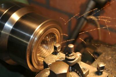 Afbeelding van het draaien van een metalen onderdeel van een klok in Restauratieatelier Heerewaarden